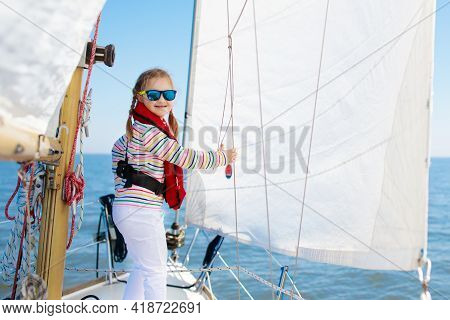 Kids Sail On Yacht In Sea. Child Sailing On Boat. Little Girl In Safe Life Jackets Travel On Ocean S