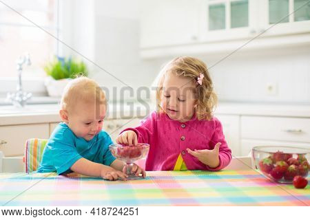 Child Having Breakfast. Kid Drinking Milk And Eating Cereal With Fruit. Little Boy And Girl At White