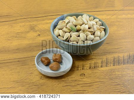 Pistachio Toffee Candy In Candy Dish With Pistachio Nuts In Shells In Ceramic Bowl