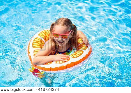 Child In Swimming Pool Floating On Toy Ring. Kids Swim. Colorful Yellow Float For Young Kids. Little