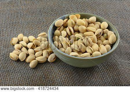 Pistachio Nuts In Shells In Ceramic Snack Bowl On Gray Burlap