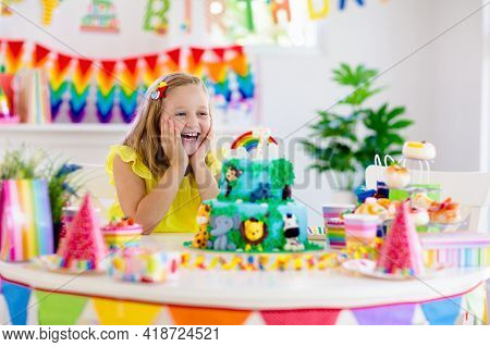 Kids Birthday Party. Child Blowing Candles On Cake And Opening Presents On Jungle Theme Celebration.