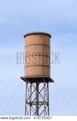 Wooden Retro Water Tower Against Blue Sky With Light Clouds