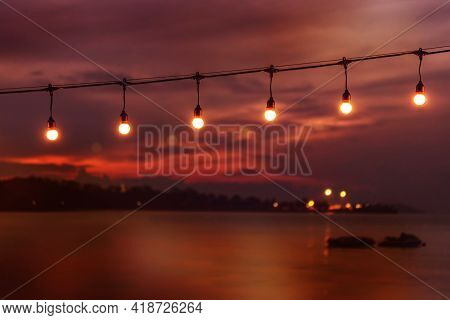 Blurred Bokeh Light On Sunset With Yellow String Lights Decor In Beach Restaurant, Tranquility Of Se