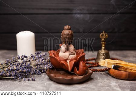 Statuette Of Buddha Incense Sticks At Workplace. Abstract Picture Of A Modern Interior In Oriental S