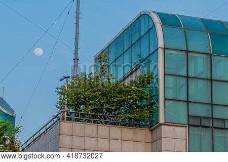 Full Moon Rising In Early Evening Over Building Between To Steel Cables.
