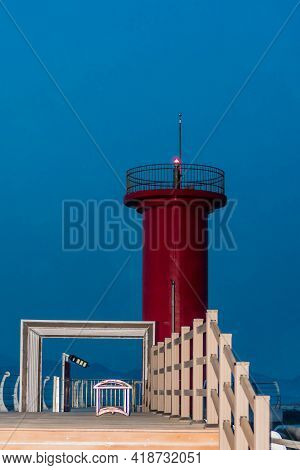 Red Lighthouse Behind Wooden Walkway On Pier With Blue Sky In Background.