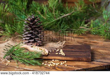 Pine Cone On A Board With Pine Nuts. Pine Branches With Green Needles Lie Around On The Table. Decor
