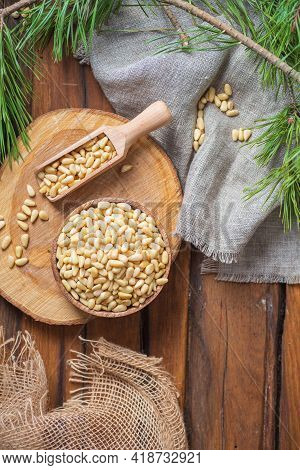 A Round Board On A Wooden Table. On It Is A Bowl Of Peeled Pine Nuts. Nearby There Is A Rough Cloth,