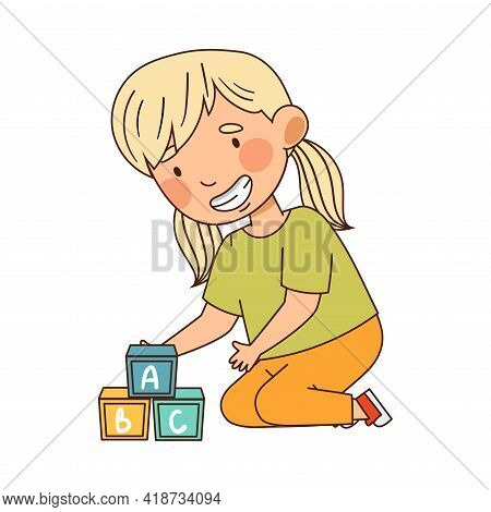 Little Blond Girl With Ponytails In Kindergarden Sitting On Floor And Learning English Alphabet With