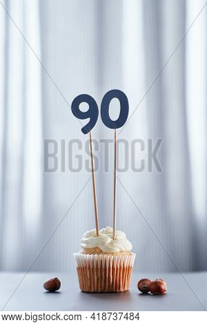 Tasty Homemade Vanilla Anniversary Cupcake With White Creamy Topping And Number 90 Ninety With Brigh