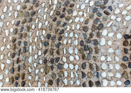 The Top View Of The Dark And White Pebbles Pathway Is A Curved Path In The Shape Of Waves In Concret