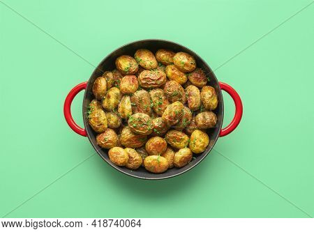 Roasted Baby Potatoes In A Cast Iron Pan Minimalist On A Green Table. Top View With A Potato Dish Ba