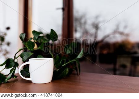 Cup Of Coffee Or Tea On The Table On The Wooden Brown Terrace During Evening Sunset With Blurred Bac