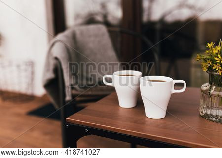 Two Cups Of Coffee On The Table On The Wooden Brown Terrace During Evening Sunset With Blurred Backg