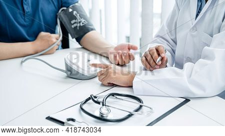 Doctor Press Blood Pressure Monitor To Measure Patient Blood Pressure, Doctor Hold Pen For Recording
