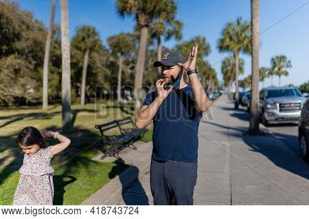 Bearded Man And Little Girl Standing On Sidewalk With Palm Trees As Background
