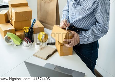 Asian Woman Small Business Owner Standing To Writing Customer Address On Parcel Of Box And Checking