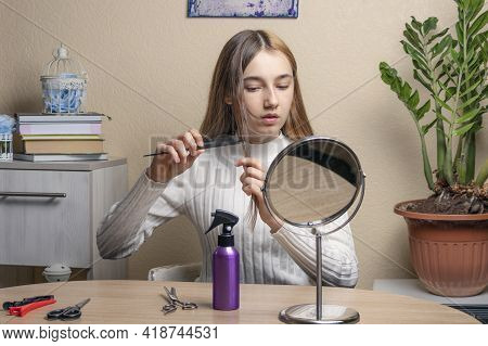 Teenage Girl With A Comb In Her Hand Looks In The Mirror. Beautiful Teenage Girl Doing Her Hair In F