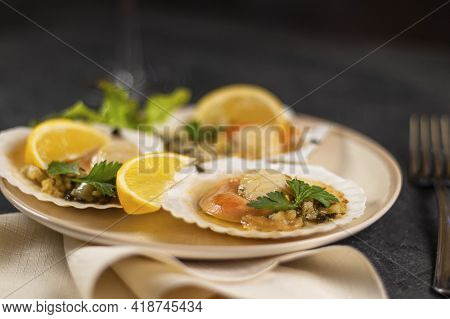 Baked Scallops With Caviar In A Plate Against The Background. Scallops With Lemon On A Black Backgro