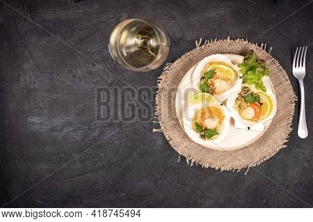Baked Scallops With Caviar In A Plate And Glass Of White Wine. Scallops With Lemon On A Black Backgr