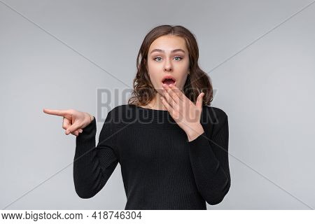 Portrait Of Young Brunette Woman, Pointing Left And Inviting People Look Promo, Standing Against Gra