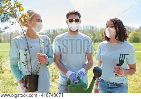volunteering, health and ecology concept - group of volunteers wearing face protective medical masks for protection from virus disease with tree seedlings and watering can in park