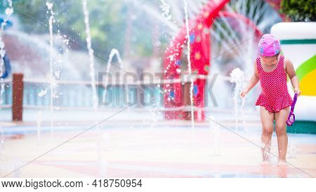 Cute Asian Girl Is Joyfully Stepping On Fountain Rising From Ground. Kid In Red Swimming Suit Is Pla