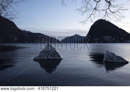Lugano / Switzerland - December 20, 2019: Lugano Lake View With Helidon Xhixha Sculpture, Lugano, Sw
