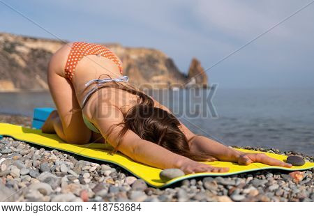 Young Woman In Swimsuit With Long Hair Practicing Stretching Outdoors On Yoga Mat By The Sea On A Su