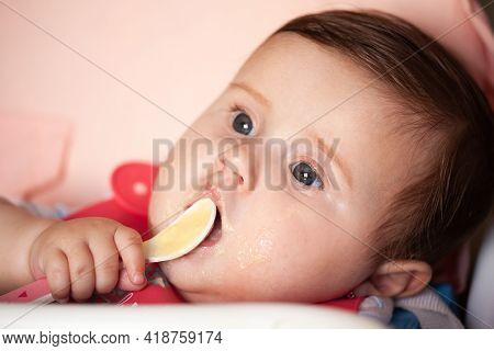 Baby Is Smeared With Porridge, Eats And Looks Into The Camera.