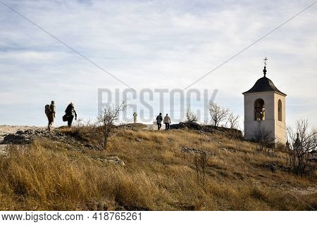 People Tourists Climb Mountain The Ancient Stone Cross And Monastery Chapel With Bell Tower. Religio