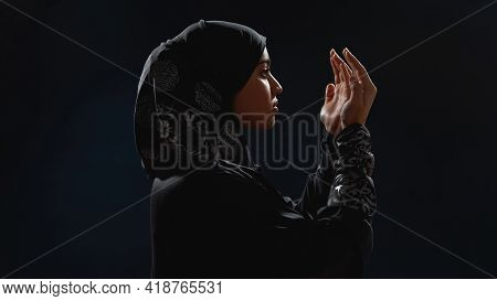 Young Arabian Woman In Hijab Standing Sideways To Camera With Open Palms In Front Of Her Face On Dar