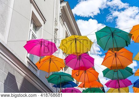 Background Colorful Umbrellas Street Decorations. Umbrellas Red And White On The Street Of The Old C