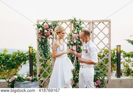 The Bride And Groom Stand Near The Wedding Arch, The Groom Puts The Ring On The Brides Finger During