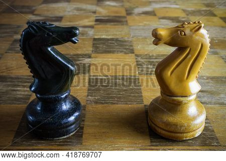 Black And Yellow Wooden Horses On Old Chessboard.