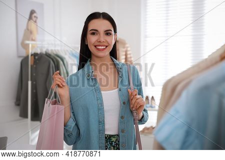 Young Woman Holding Shopping Bag Near Rack With Clothes In Modern Boutique