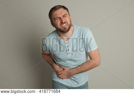 Man Suffering From Acute Appendicitis On Light Grey Background
