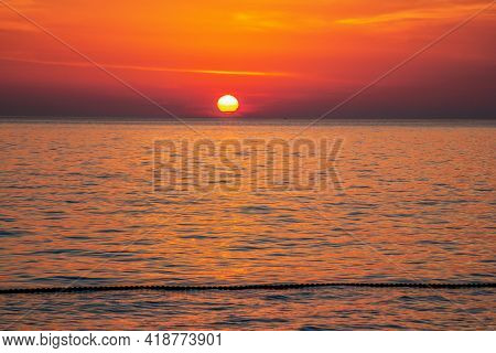 Beautiful Landscape - Beach On Sunset - Red And Orange Sky And Sunlight Reflecting On Sea Water.