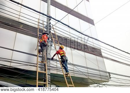 Bangkok, Thailand - July 18, 2017 : Technician Workers Are Climbing Up To Monitor, Wiring, Repair Cc