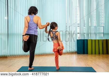 Mother And Her Daughter In Preschool Age Practicing Balancing Yoga Pose With One Leg Up Together In