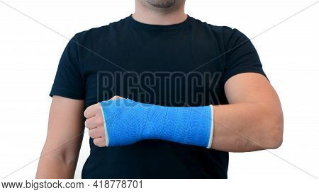 Unrecognizable Man In A Black T-shirt Shows Hand Wrapped In A Fiberglass Plaster Cast On A White Bac