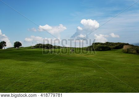 Hilly Ridge With Green Grass And Trees In The Background In Galicia, Spain