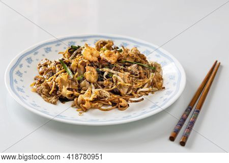 Serving Of Simple Penang Char Kuey Teow Is Popular Fried Noodle With Coceral, Shrimp And Eggs In Bla
