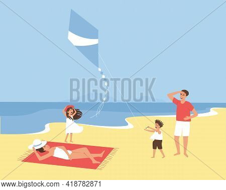 Family On Vacation At The Seaside. Children Fly A Kite On The Seashore. A Strong Wind Blows The Kite