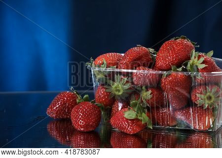 Strawberries In A Plastic Box Closeup In A Dark Blue Background. Healthy Lifestyle. Multivitamin Coc