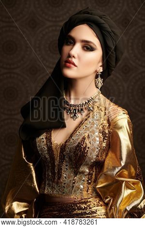 Portrait of a beautiful arabian woman in traditional dress, with traditional oriental make-up and black turban. Make-up and cosmetics. Oriental beauty woman.