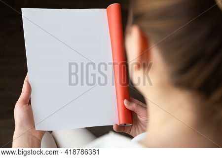 Top View Of A Woman Reading An Open Book Or Magazine. Empty Page. Mock Up