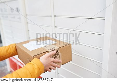 The Girl Stands Near The Post Office And Sends The Package To The Parcel Locker. Receiving Package.