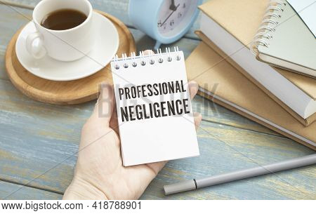 Concept Professional Negligence Message On A White Sticker With Pen On Hands.